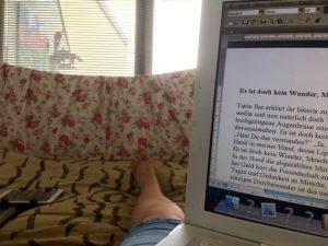 Laptop und Bein im Bett